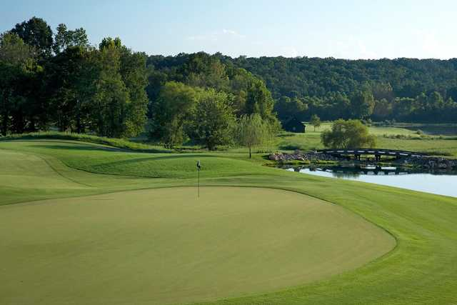 A view of a green and a bridge in background at Barnsley Resort.