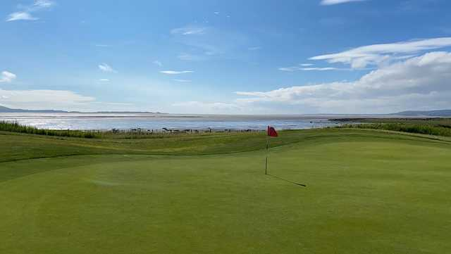 A sunny day view of a green at Machynys Peninsula Golf & Country Club.