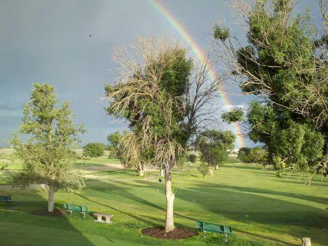 A view of the rainbow over a green at Artesia Country Club.