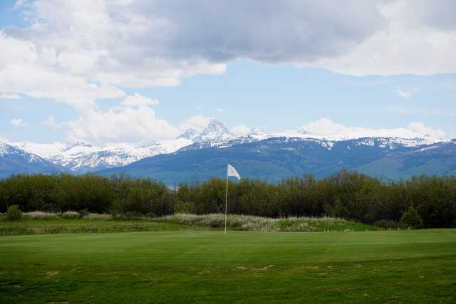 A view of a green and mountains covered by snow in the distance from The Links at Teton Peaks.