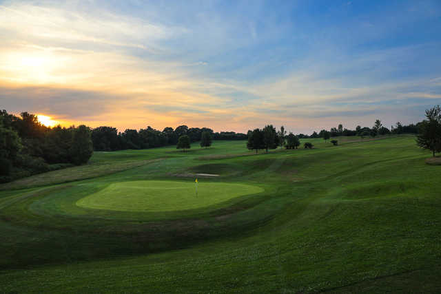A sunset view of a green at Kingfisher Course from Mannings Heath Golf Club.