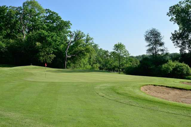 A sunny day view of a green at Chalet Hills Golf Club.