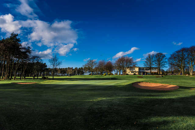 A sunny day view of a hole and the clubhouse in the distance at Westerhope Golf Club.