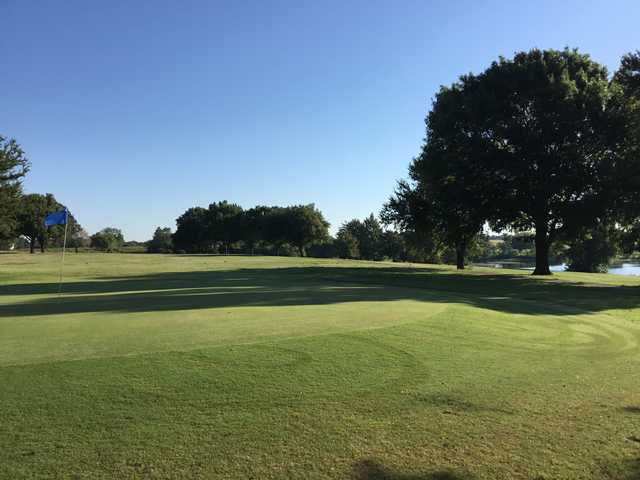 A sunny day view of a green at Waxahachie Golf Club.