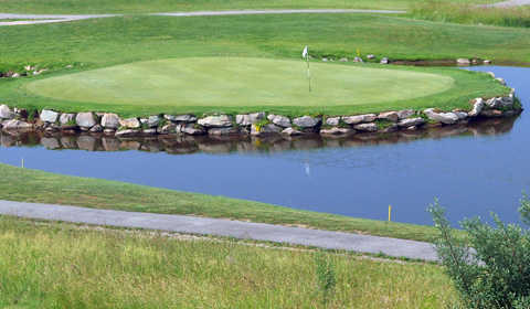 A view of the 14th hole surrounded by water at Raven Rock Golf Course