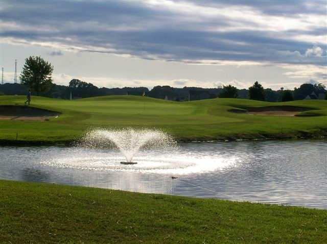 A view of green with water fountain in foreground at Hobbs Hole Golf Course