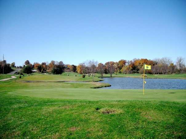 A view of green with water in background at Woodlands Golf Club