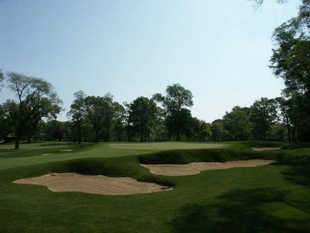 A view of a green protected by bunkers at Ravisloe Country Club