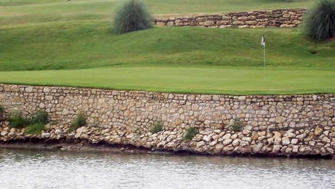 A view over the water of a green from The Golf Club at the Resort