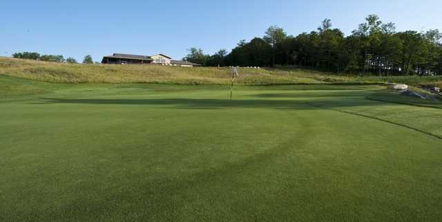 A view of a green with clubhouse in background at Mill Creek Golf Club.