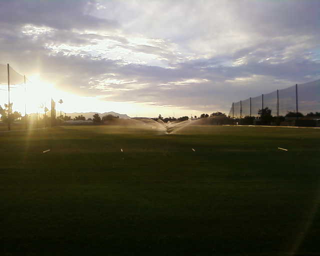 A sunny view of the driving range at Desert Sands Golf Course