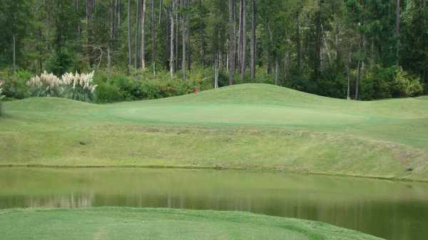 A view over the water of the 2nd green at Country Oaks Golf Course
