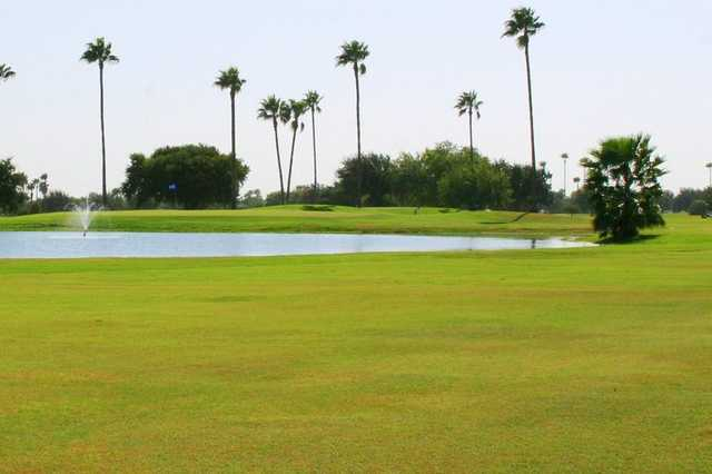 A view of a green with water fountain in foreground at Howling Trails Golf Course.