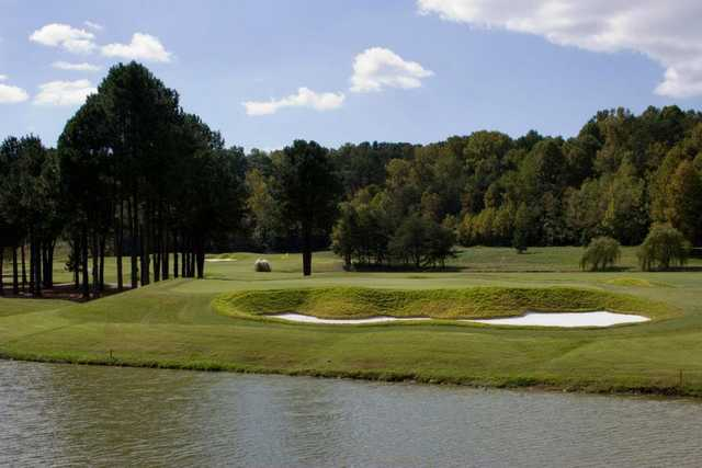 A view over the water of green protected by bunker at Cross Creek Country Club