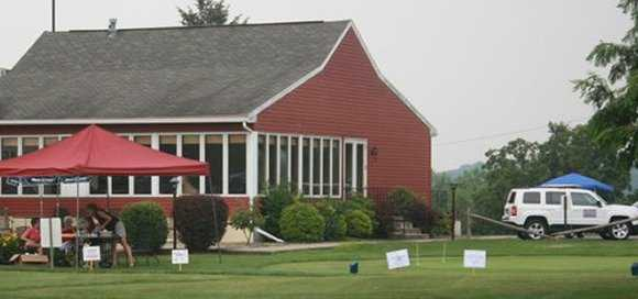 A view of the clubhouse and the putting green at Wynding Brook Golf Club