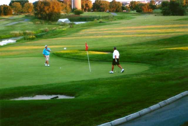 A view of a green with a water fountain in backgound at Broken Arrow Golf Club