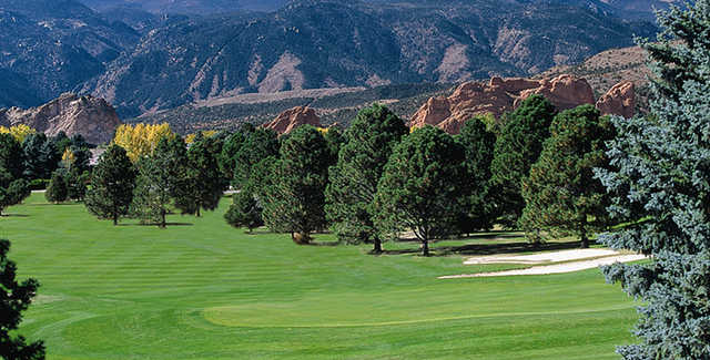 A view of a green with mountains in background at Garden of the Gods Club.