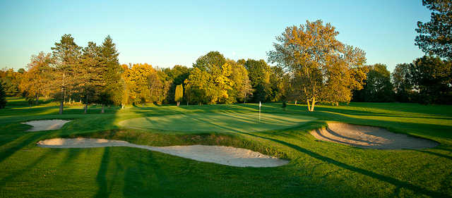 A sunny view of a green guarded by bunkers at The Pheasant Golf Links (Michael Sigl)