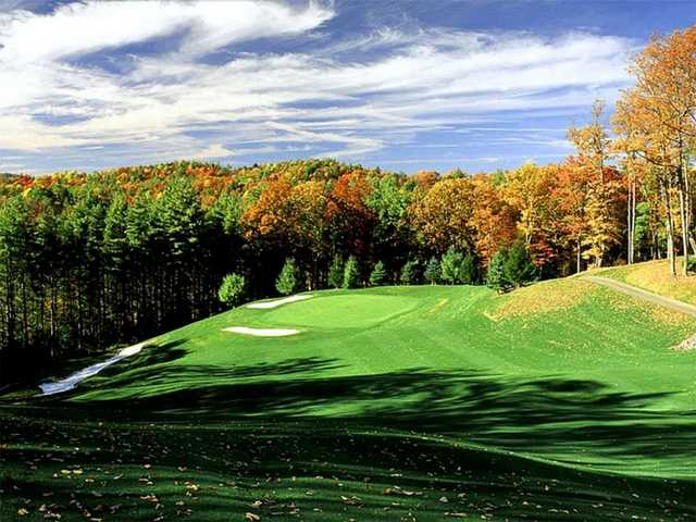 A fall view of green protected by sand traps at Black Bear Golf Club
