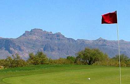 A view from green with mountains in background at Apache Creek Golf Club