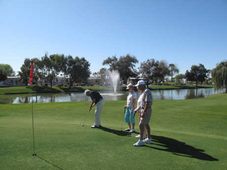 A view of a green with water fountain in background at Pueblo El Mirage Golf Club