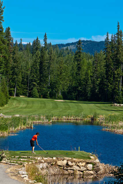 A view of a tee surrounded by water, fairway and green at Priest Lake Golf Club