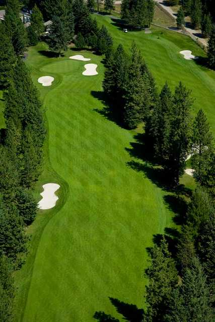 Aerial view of a fairway and green protected by bunkers at Twin Lakes Village Golf Course