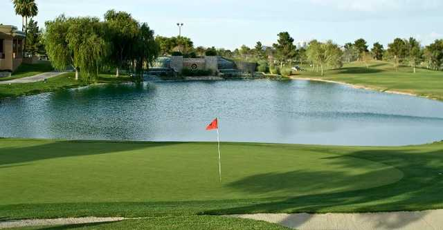 A view of a green with water in background at Spanish Trail Country Club