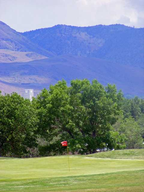 A view of a hole with mountains in background at Wildcreek Golf Course