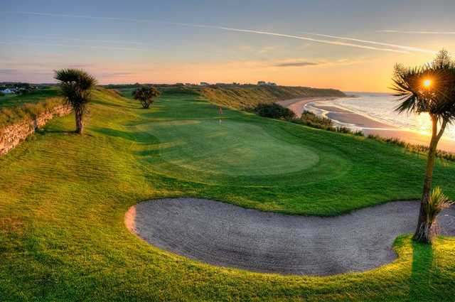 A sunny view of a green protected by sand trap at St Helens Bay Golf Resort