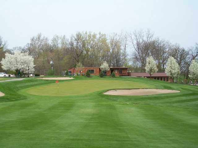 A view of green protected by sand traps and blooming trees at Cedar Creek Golf Course