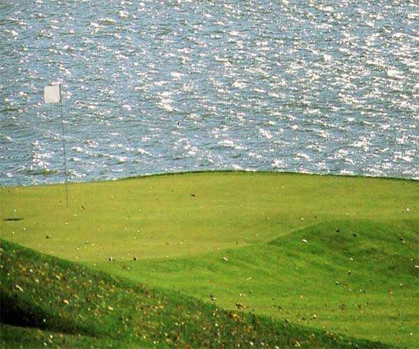 A view of the 6th green with water in background from Harbor Links at Sagamore Resort