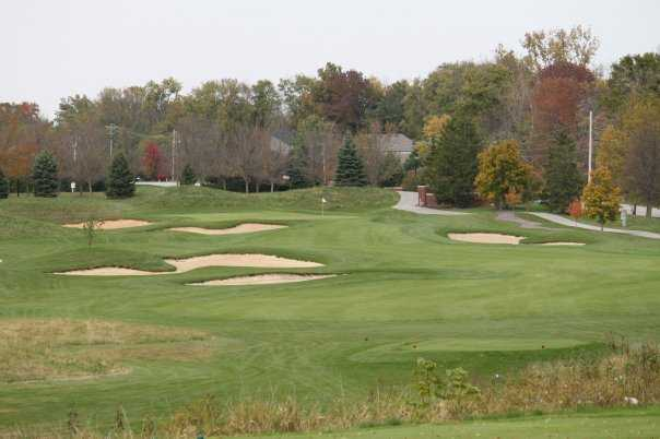 A view of a green surrounded by sand traps at West Chase Golf Club