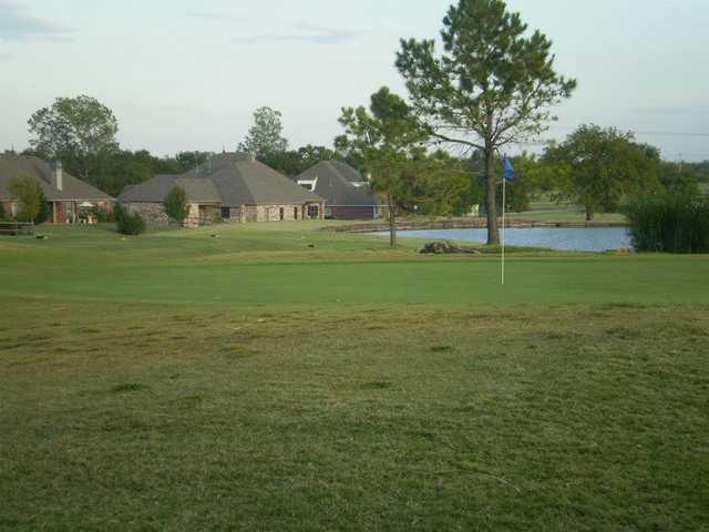 A view of a green with water in background at White Hawk Golf Club