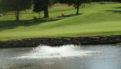 A view over the water of the signature hole #3 at Crimson Creek Golf Course