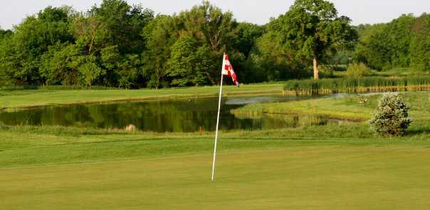 A view of green with water in background at Eagle Hills Golf Course