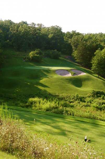 A view of a green guarded by sand traps at Old Kinderhook Golf Course