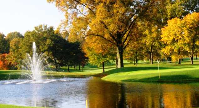 A sunny fall view of green with water fountain on the left side at Kendale Course from Kenwood Country Club