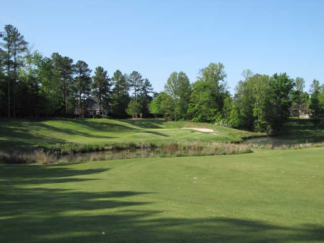 A view of a green protected by bunkers at River Falls Plantation