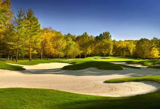 A view of a green surrounded by sand traps at Lakewood Country Club