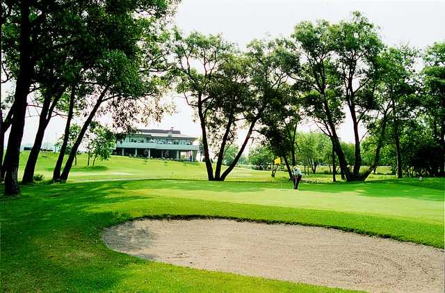 A view of the clubhouse with sand trap in foreground at Harmony Creek Golf Club