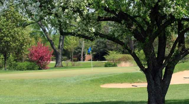 A spring view of a hole with a sand trap on the right side at Deer Path Golf Course