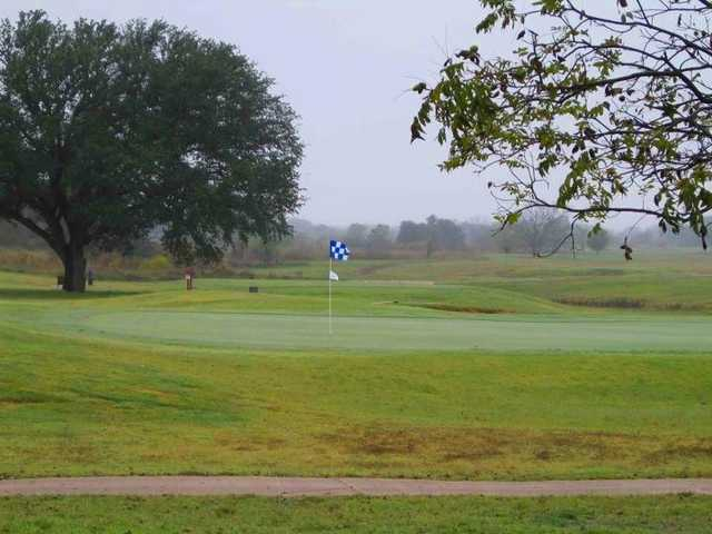A view of a green with narrow path in foreground at Concho Springs Golf Course