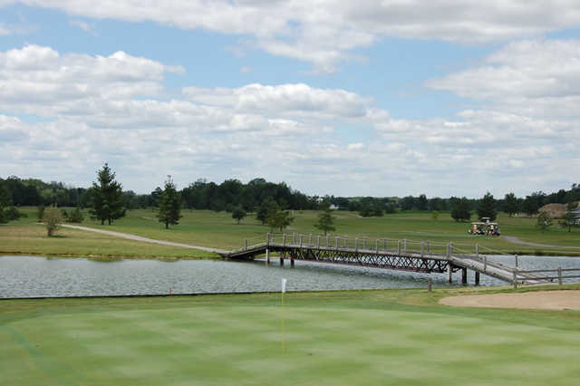 A view of a green with a bridge in the background at Holly Meadows Golf Course