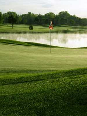 A view of green with water in background at Players Club from Woodland Trails