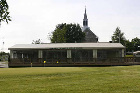 A view of the clubhouse and practice putting green at Gilbertsville Golf Club