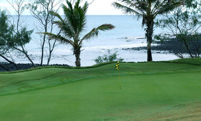 A view of green with water in background at Coral Cove Golf Club
