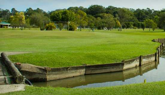 A view of green surrounded by water at Meadow Park Golf Course