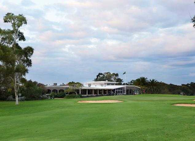 A view of green flanked by bunkers with clubhouse in background at Royal Fremantle Golf Club