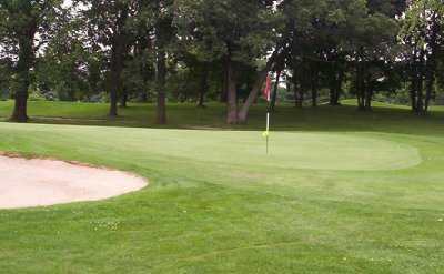 A view of a green protected by a bunker at Delbrook Golf Club